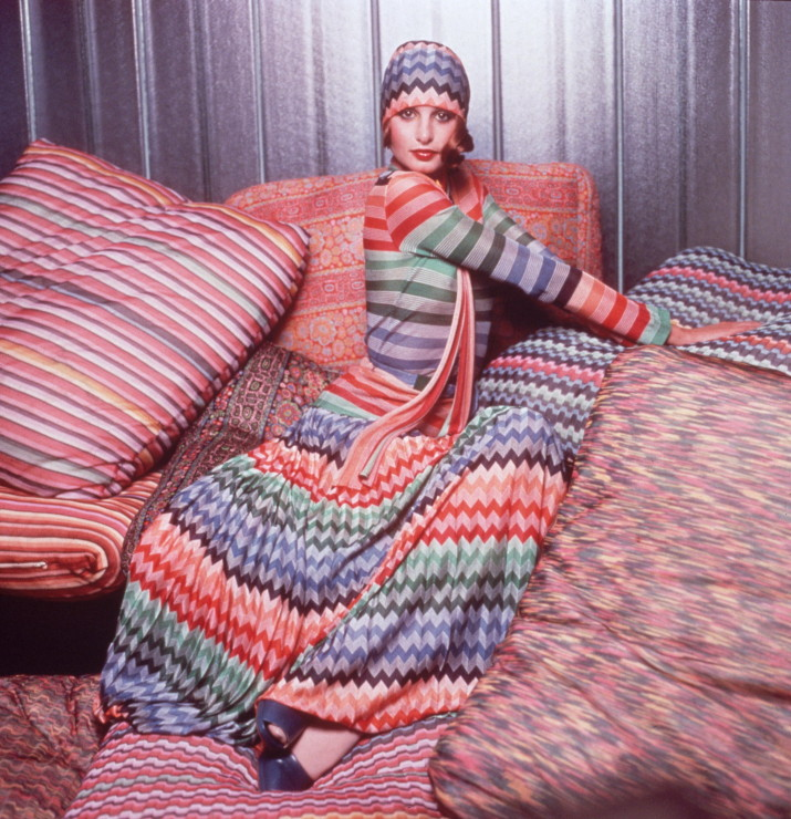 Portrait of a model wearing a colorful outfit designed by Missoni while posing on pillows covered in Missoni fabric. The outfit consists of a herringbone weave head scarf and maxi skirt and a striped top. (Photo by Hulton Archive/Getty Images)
