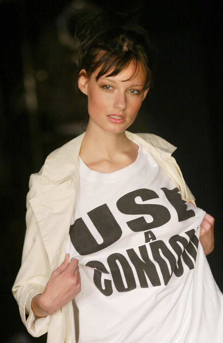 """A model displays her outfit which reads """"Use a Condom"""" during Katharine Hamnett's spring/summer 2004 collection show 24 September 2003 for London Fashion Week. AFP PHOTO/Jim WATSON (Photo credit should read JIM WATSON/AFP/Getty Images)"""