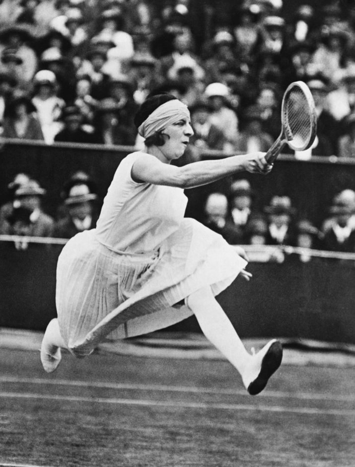 (Original Caption) Mlle. Suzanne Lenglen, for the fifth consecutive year won the woman's singles tennis championship at Wimbledon. Her opponent in the finals, Miss McKane, English champion, played brilliantly but without avail, succumbing to the French star in straight set 6-2, 6-2. This remarkable action photo, just received from England, shows the French star in mid-air. (Photo by George Rinhart/Corbis via Getty Images)